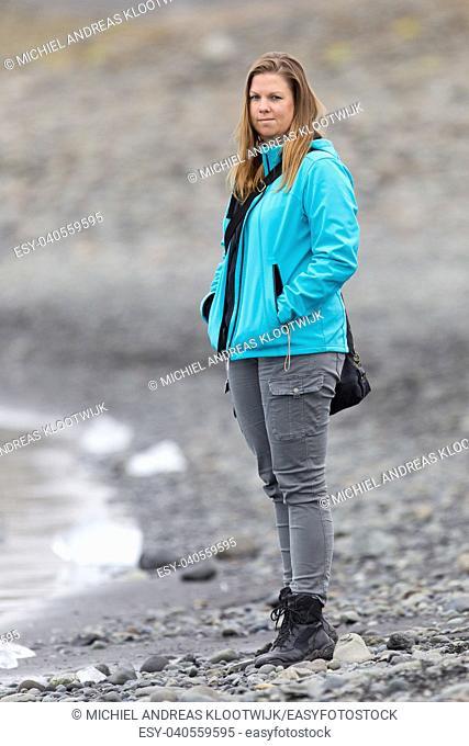 Woman walking over the beach at Jokulsarlon glacier lagoon in southern Iceland