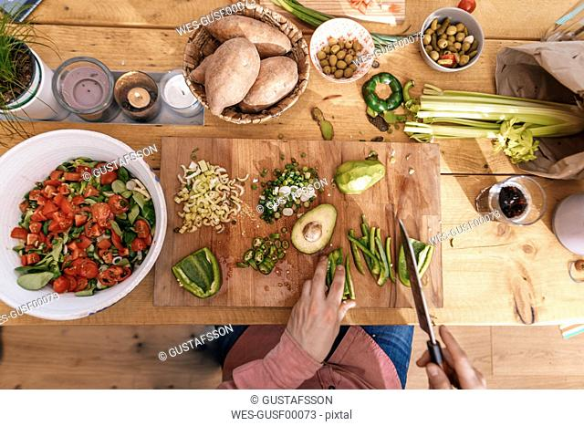 Man chopping vegetables in the kitchen, top view