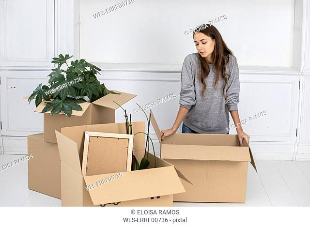 Woman standing in new home with cardboard boxes