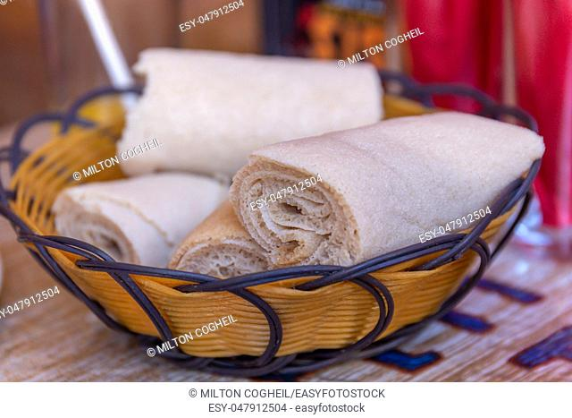 Rolls of Injera in a serving bowl. Injera is a sourdough flatbread made from teff flour. It is the national dish of Ethiopia, Eritrea, Somalia and Djibouti