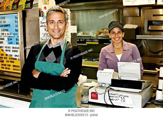 Hispanic servers smiling in restaurant