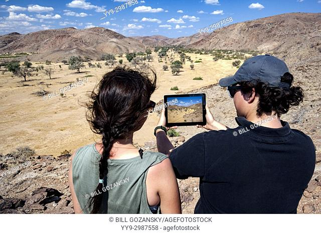 Couple taking picture with tablet in Damaraland - Huab Under Canvas, Damaraland, Namibia, Africa