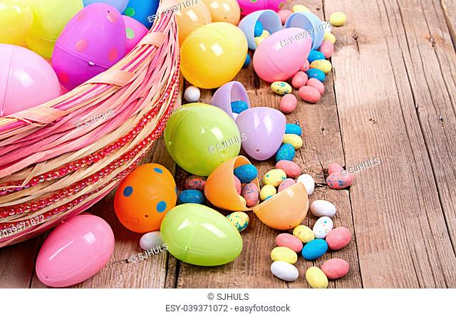 Plastic easter eggs filled with candy in a Easter basket on a wooden background