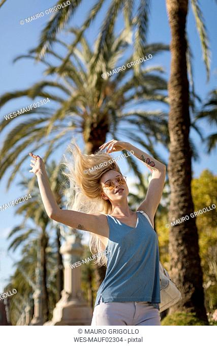 Carefree young woman moving under palm tree