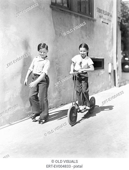Boy and girl playing on a scooter and the other on roller blades All persons depicted are not longer living and no estate exists Supplier warranties that there...