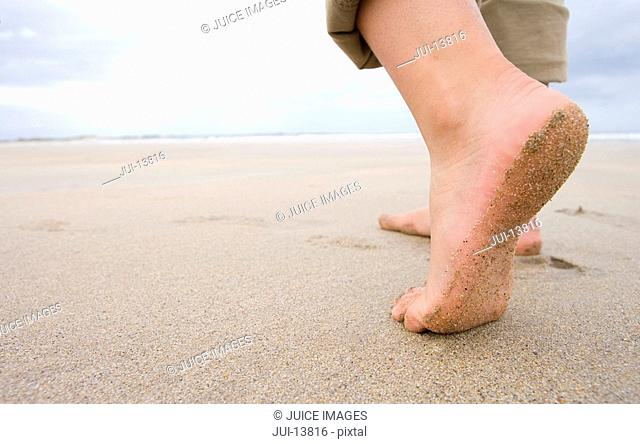 Woman on beach, close-up of feet, low section