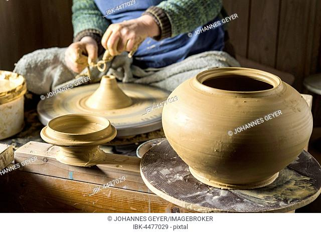 Ceramics workshop, pot and lid at front, hands on pottery wheel at back, Pittenhart, Upper Bavaria, Germany