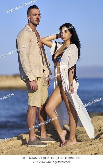 attractive couple at Mediterranean beach. Greek ethnicity. In holiday destination Hersonissos, Crete, Greece