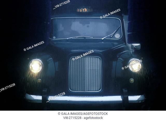 SINGLE BLACK TAXI CAB GOING THROUGH AUTOMATIC CAR WASH LONDON ENGLAND UK