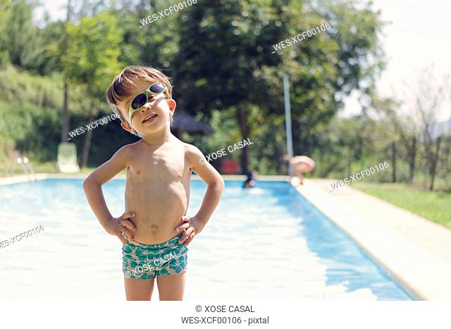 Portrait of little boy with sunglasses standing in front of swimming pool