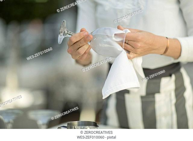 Close-up of waitress cleaning wine glass