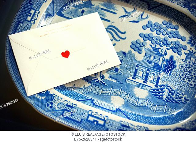 Blue willow pattern china dish with a Valentines card with a heart in the envelope