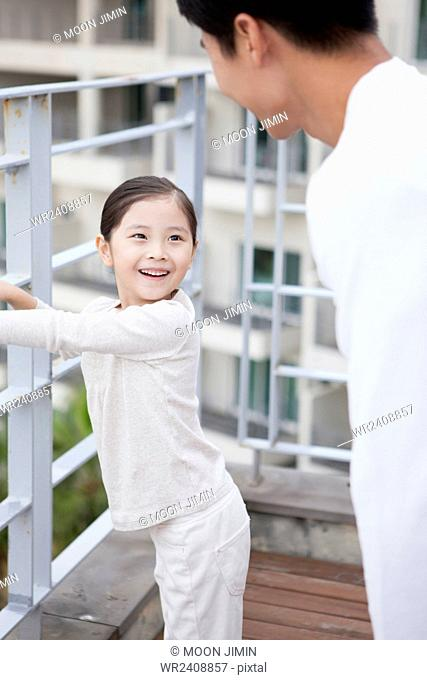 Daughter looking at her father with a smile at the resort balcony