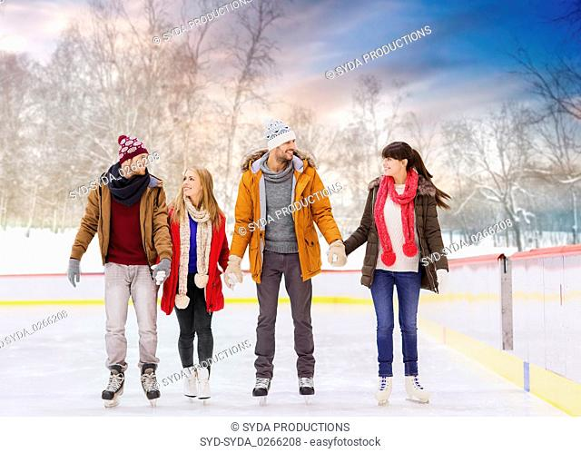 happy friends on outdoor skating rink