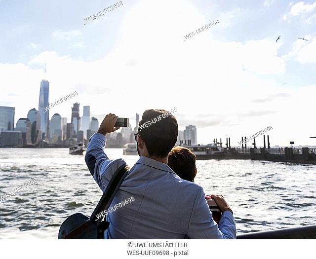 USA, man and woman at New Jersey waterfront with view to Manhattan taking cell phone picture