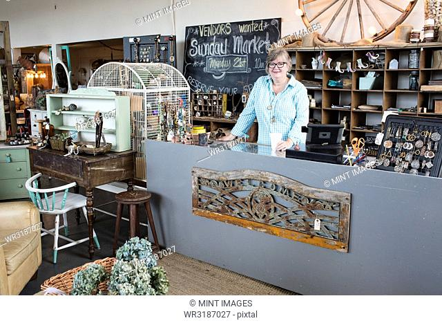 Caucasian woman owner of an antique store standing near the cash register