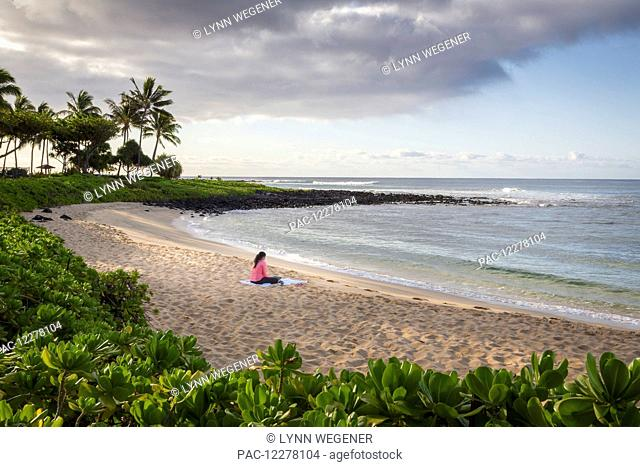 A young woman works on her computer on a beach in the early morning; Poipu, Kauai, Hawaii, United States of America