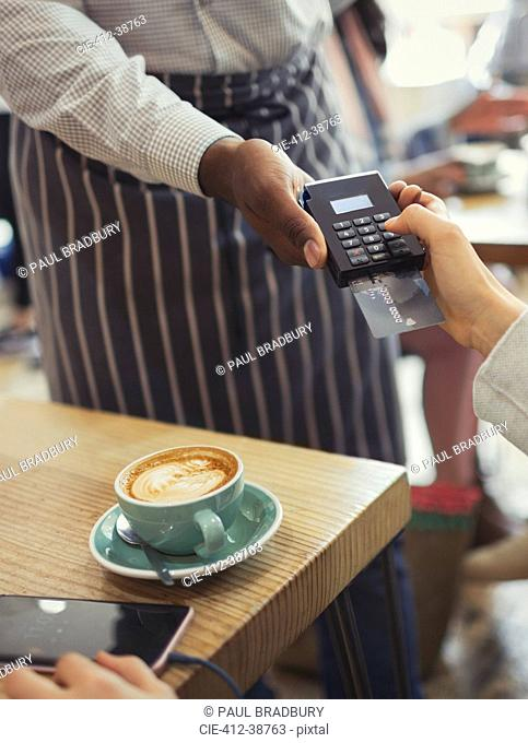Customer paying waiter with credit card reader at cafe table