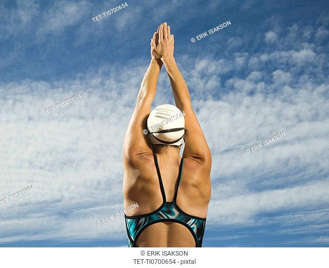 Rear view of female swimmer with arms raised, Utah, United States