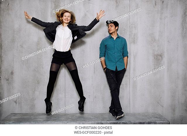 Couple in front of concrete wall, woman jumping