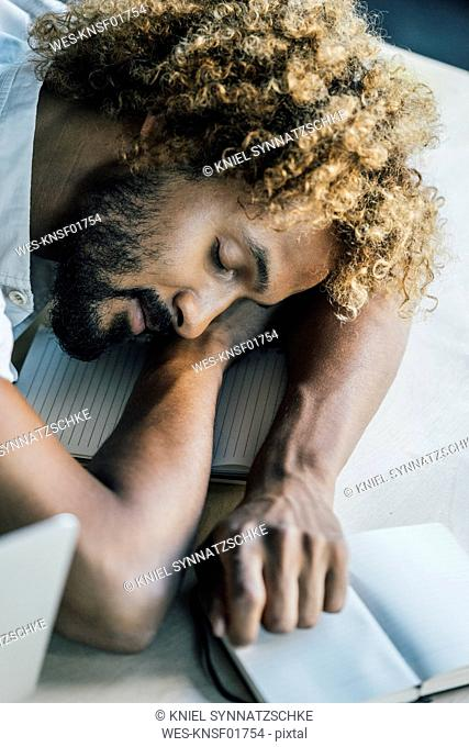 Young man lying on desk sleeping