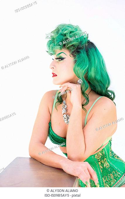 Woman with dyed green hair wearing corset looking away