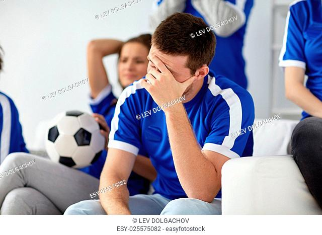 friendship, leisure, sport and entertainment concept - unhappy man with friends or football fans at home