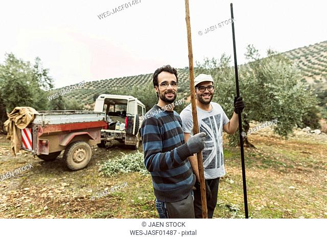 Spain, portrait of two smiling workers with tools in olive grove
