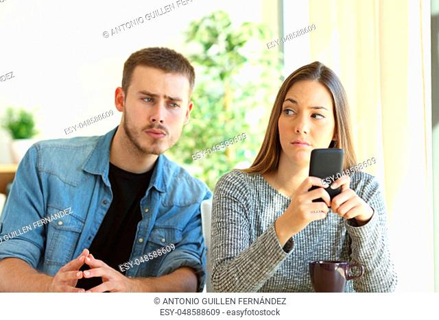 Jealous boyfriend spying his girlfriend watching her phone while she is looking him upset