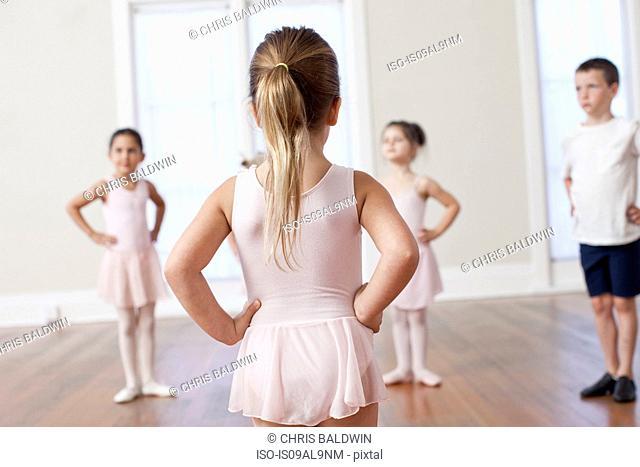Four children practicing ballet with hands on hips in ballet school