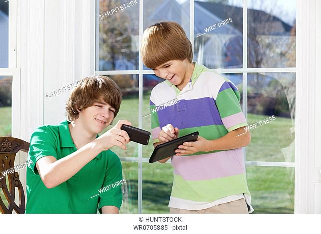 Two boys using a digital tablet and a smart phone
