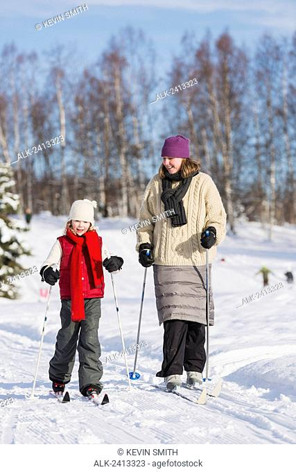 Mother and young daughter cross country skiing in a wooded park, Russian Jack Springs city park, Anchorage, South Central Alaska, USA