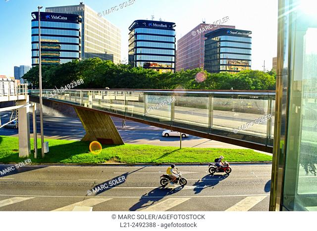 Two motorcyclists passing under Ildefons Cerdà Square Bridge, La Caixa buildings in background. Barcelona, Catalonia, Spain