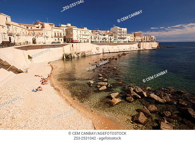 People sunbathing at the small beach, Ortigia island, Syracuse, Sicily, Italy, Europe