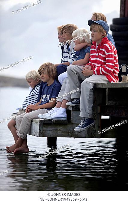 Children sitting on jetty, Vastkusten, Sweden