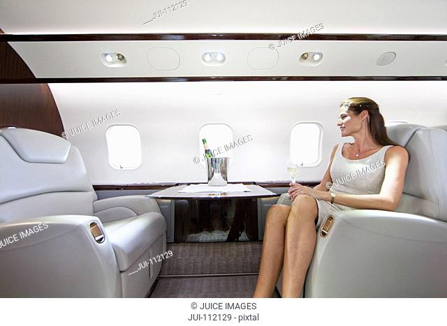 Attractive woman sitting and holding champagne glass in private jet