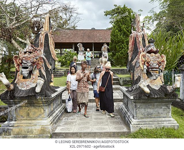 Tourists with a local guide in the Tirta Gangga water palace, a former royal palace. Karangasem regency, Bali, Indonesia