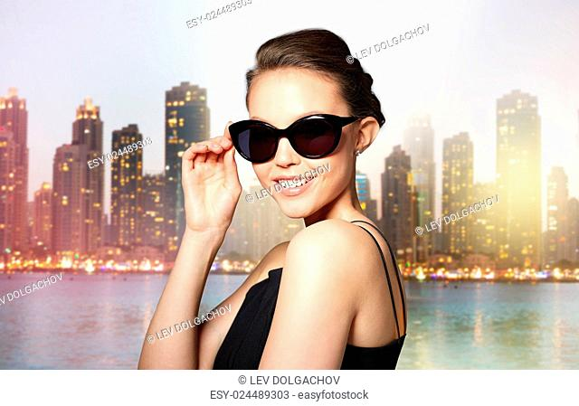 accessories, eyewear, fashion, people and luxury concept - beautiful young woman in elegant black sunglasses over dubai night city lights street background