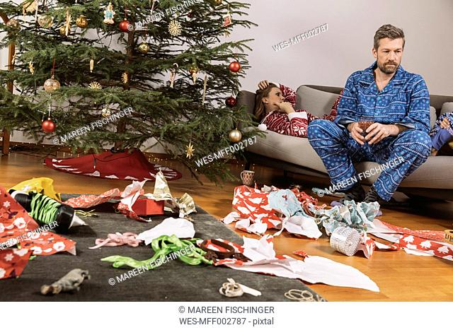 Tired couple in Christmas pyjamas looking at mess of wrapping paper