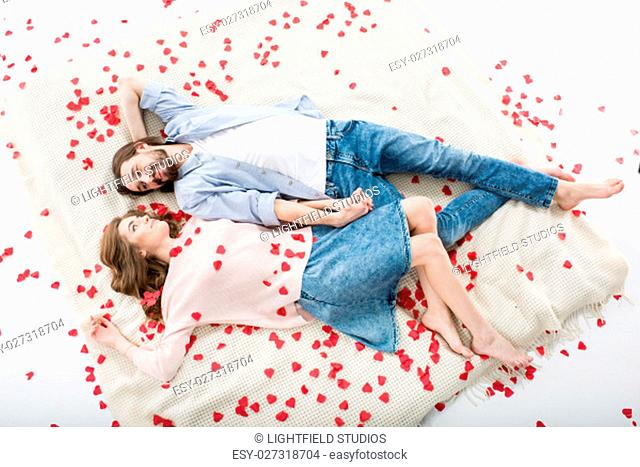 Beautiful couple in love lying and looking at each other on red paper hearts