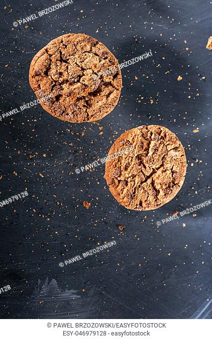 Group of chocolate cookies with crumbles flying over the black background. Close up