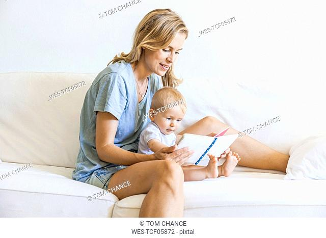 Mother and baby girl sitting on couch looking at picture book