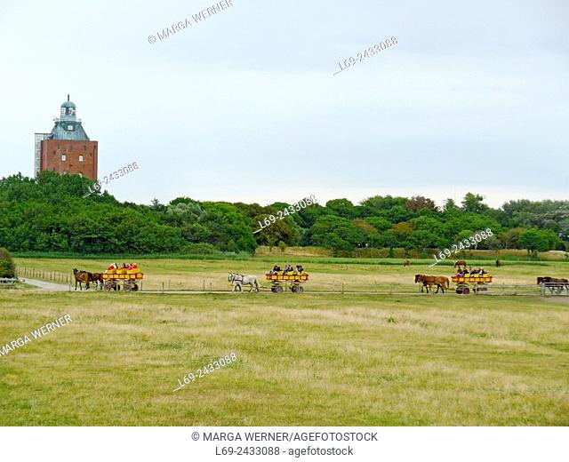 'Wattwagen' in front of Historic lighthouse from 1310 on island Neuwerk, Elbe estuary, North Sea, Hamburg, Germany