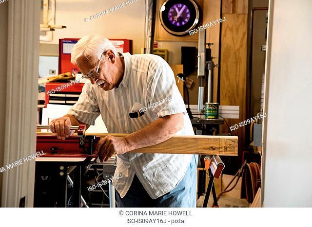 Senior man placing woodblock on carpentry equipment workshop
