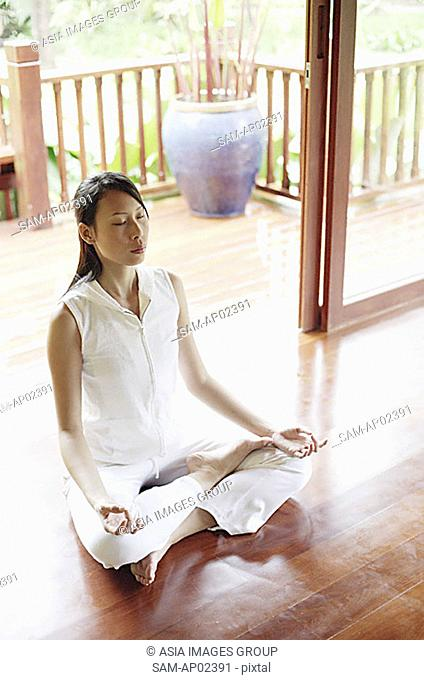 Woman practicing yoga, sitting in lotus position