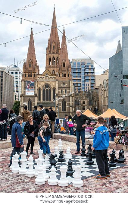 Open-air chess game in Federation Square, Melbourne, with St Paul's Cathedral beyond