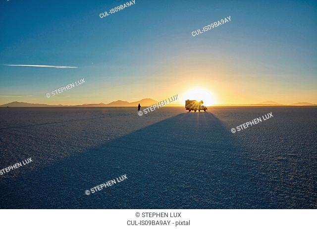 Woman exploring salt flats, recreational vehicle in background, Salar de Uyuni, Uyuni, Oruro, Bolivia, South America