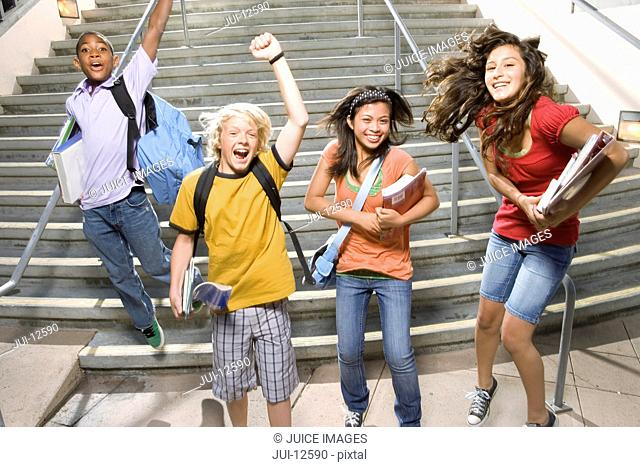 Small group of teenagers 11-15 jumping from steps outdoors, cheering, portrait