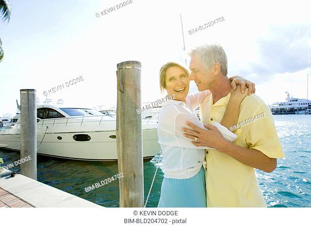 Caucasian couple hugging on dock