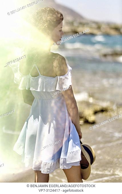 woman on beach, sunlight, reflections, thoughtful, in Hersonissos, Crete, Greece